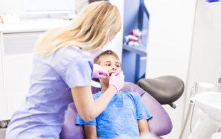Una dentista atiende a un niño en consulta.